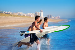 Personas que practica surf de los muchachos que practican surf el salto de funcionamiento en las tablas hawaianas Fotografía de archivo libre de regalías