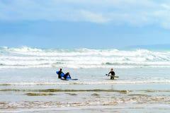 Personas que practica surf de sexo femenino con los tableros que practican surf Fotografía de archivo
