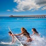 Personas que practica surf del adolescente que corren el salto en las tablas hawaianas Imagen de archivo libre de regalías