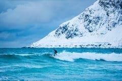 Personas que practica surf del entrenamiento en aguas frías de Lofotens Fotografía de archivo