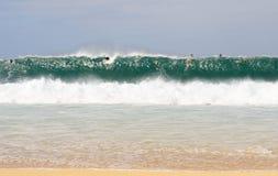 Personas que practica surf del océano en distancia Foto de archivo