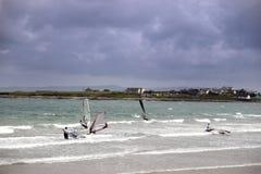 Personas que practica surf del viento que hacen frente a la tormenta salvaje Fotos de archivo