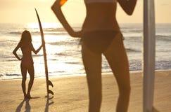Personas que practica surf en bikiníes y tablas hawaianas en la playa de la puesta del sol foto de archivo
