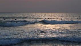 Personas que practica surf en el océano almacen de metraje de vídeo