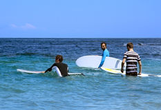 Personas que practica surf en el océano con los tableros de resaca Fotos de archivo libres de regalías