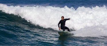Personas que practica surf en la acción Foto de archivo