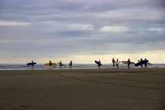 Personas que practica surf en la oscuridad en la playa de 90 millas, Ahipara, Nueva Zelanda Imagenes de archivo