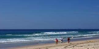 Personas que practica surf en la playa Fotografía de archivo