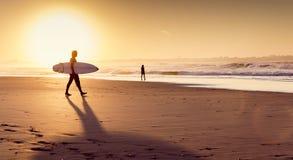 Personas que practica surf en la playa imagen de archivo