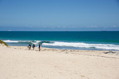 Personas que practica surf en la playa de la ciudad Imagenes de archivo