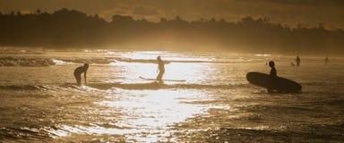 Personas que practica surf en la playa del océano en la puesta del sol Imagen de archivo