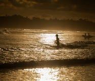Personas que practica surf en la playa del océano en la puesta del sol Fotografía de archivo libre de regalías