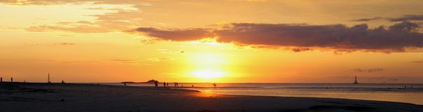 Personas que practica surf en la playa en la puesta del sol Imagen de archivo libre de regalías