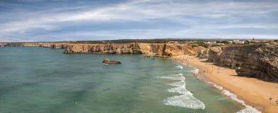 Personas que practica surf en la playa portuguesa cerca del pueblo de Sagres Fotos de archivo libres de regalías