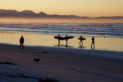 Personas que practica surf en la puesta del sol Fotografía de archivo libre de regalías