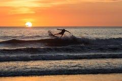Personas que practica surf en la puesta del sol en el negra de Playa, Costa Rica Fotos de archivo