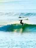 Personas que practica surf en la puesta del sol portugal Fotos de archivo libres de regalías