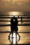 Personas que practica surf en la puesta del sol roja Fotos de archivo