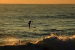 Personas que practica surf en la salida del sol Foto de archivo libre de regalías