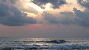 Personas que practica surf en las ondas de la tarde metrajes