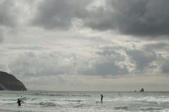 Personas que practica surf en un día nublado Fotografía de archivo libre de regalías