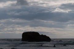 Personas que practica surf en un día nublado Imagen de archivo libre de regalías