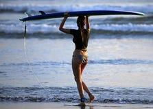 Personas que practica surf en una costa costa Imagen de archivo libre de regalías