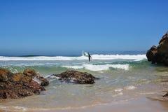 Personas que practica surf en una playa en el sout África Foto de archivo