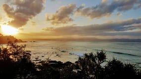 Personas que practica surf que esperan la onda pasada en la puesta del sol Foto de archivo libre de regalías