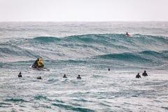Personas que practica surf que esperan la playa de la puesta del sol de las ondas Foto de archivo libre de regalías
