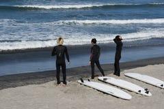 3 personas que practica surf horizontales Fotografía de archivo