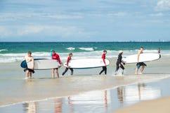 Personas que practica surf jovenes en la playa en el paraíso de las personas que practica surf Foto de archivo libre de regalías