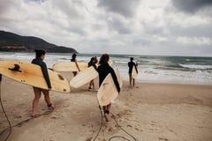 Personas que practica surf no identificadas de las mujeres con los tableros que practican surf que vienen al mar Fotografía de archivo libre de regalías