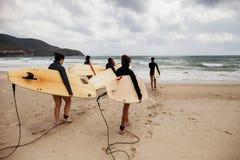 Personas que practica surf no identificadas de las mujeres con los tableros que practican surf que vienen al mar Imagenes de archivo