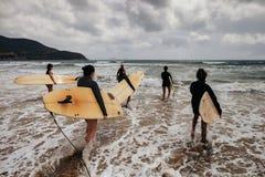 Personas que practica surf no identificadas de las mujeres con los tableros que practican surf que vienen al mar Imagen de archivo
