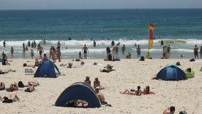 PERSONAS QUE PRACTICA SURF PARADISE, AUSTRALIA DICIEMBRE, 4, 2016: turistas y asistentes de la playa en mainbeach en el paraíso d almacen de metraje de vídeo