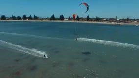 Personas que practica surf profesionales kiteboarding en el océano azul claro en paisaje marino tropical del día soleado en la op almacen de metraje de vídeo