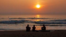 Personas que practica surf que admiran la puesta del sol Imágenes de archivo libres de regalías