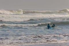 Personas que practica surf que esperan la onda Imagen de archivo