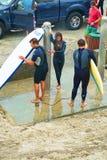 Personas que practica surf que lavan las tablas hawaianas en la playa del sello foto de archivo