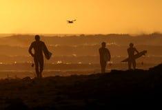 Personas que practica surf que recorren abajo de la playa en la puesta del sol Foto de archivo