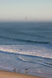 Personas que practica surf que recorren a lo largo de la playa Foto de archivo libre de regalías