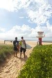 Personas que practica surf que van para la resaca de la mañana Fotos de archivo libres de regalías