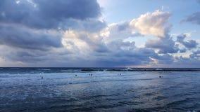 Personas que practica surf silueteadas con el fondo colorido del cielo y del mar Imagen de archivo