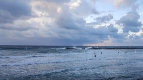 Personas que practica surf silueteadas con el fondo colorido del cielo y del mar Imagenes de archivo