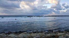 Personas que practica surf silueteadas con el fondo colorido del cielo y del mar Fotos de archivo