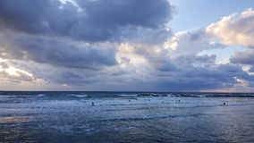 Personas que practica surf silueteadas con el fondo colorido del cielo y del mar Foto de archivo