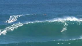 Personas que practica surf y jetski en los mandíbulas de la rotura de la onda que practican surf grande en la orilla del norte de almacen de video