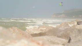 Personas que practica surf y kitesurfers en el mar
