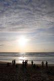 Personas que practica surf y nadadores en la playa Imagenes de archivo